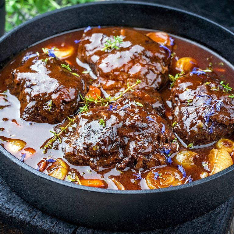 Traditional German braised beef cheeks in brown red wine sauce with carrots and onions offered as closeup in a cast iron Dutch oven on an old rustic cutting board