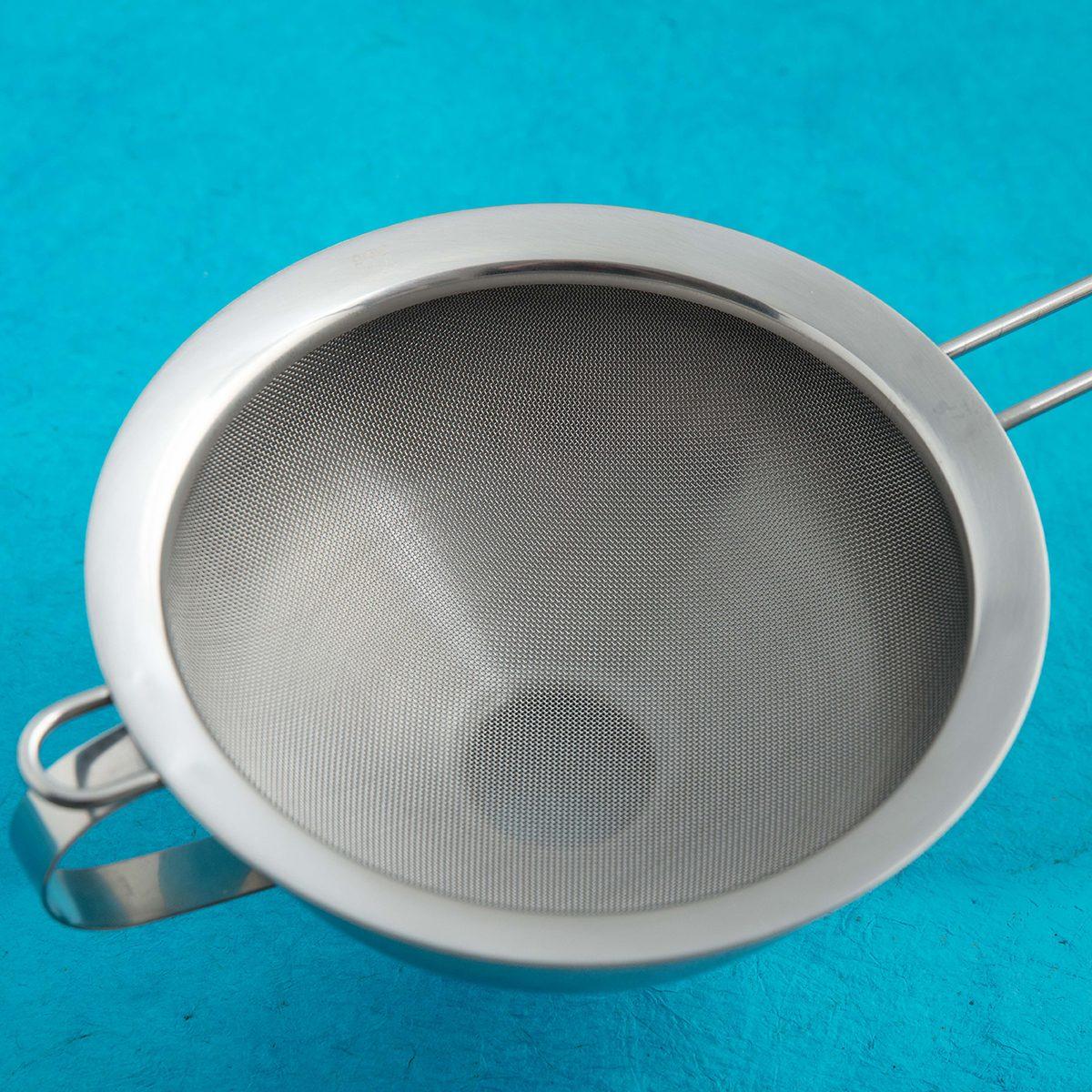 Stainless steel funnel with sieve insert. Blue kitchen background.