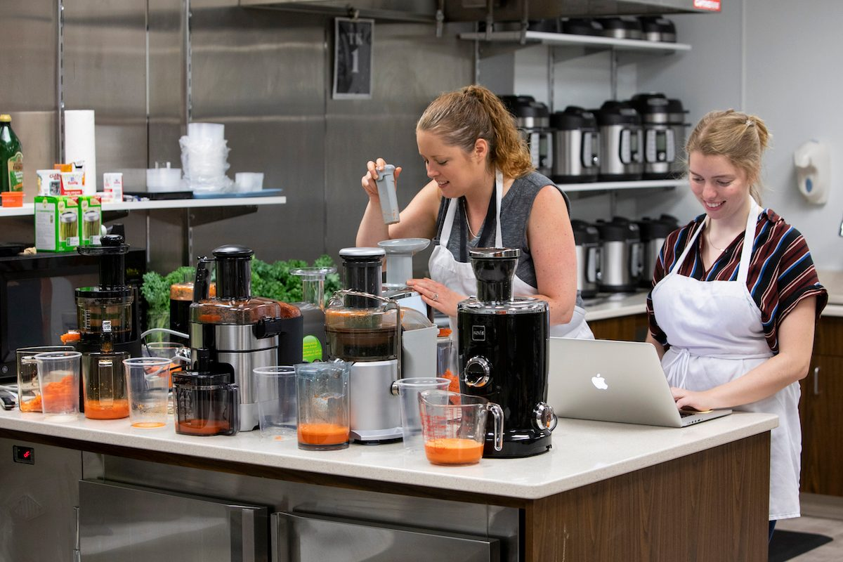 Shannon Norris and Audrey Rompon testing juicers in the Taste of Home Test Kitchen.