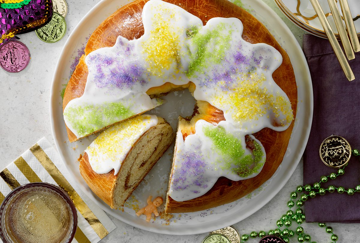 Traditional New Orleans King Cake; Overhead camer angle; White russian speckled surface; champagne; gold accents; gold flatware; Mardi Gras decorations; baby figure