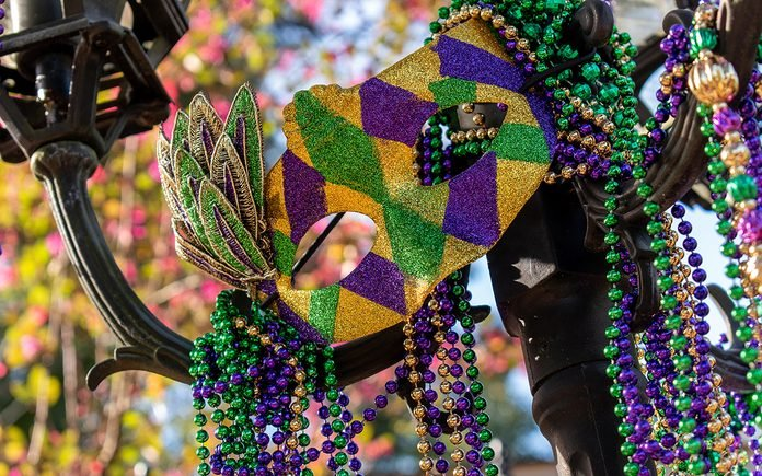 Outdoor Mardi Gras beads and mask on light post in sunshine