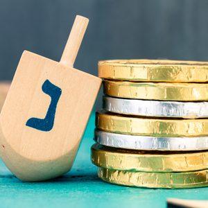 Hanukkah dreidels with some Hanukkah coins and Hanukkah candles on a vintage wood green background. Translation of the hebrew text: Letter N
