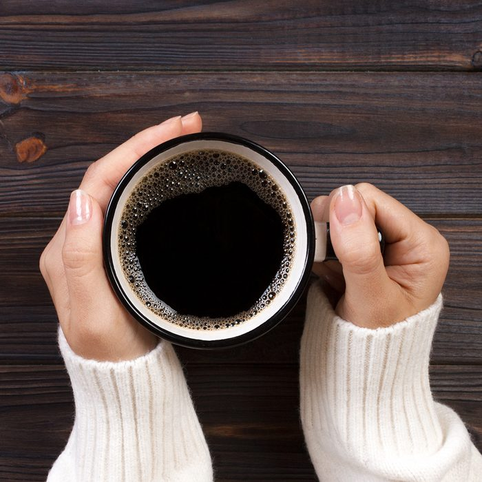 Directly Above Shot Of Woman Hands Holding Black Coffee In Cup On Table