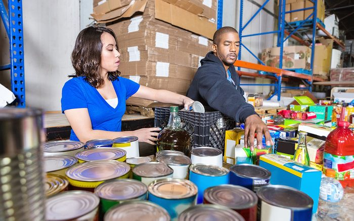Young people volunteering to sort donations for charity food drive