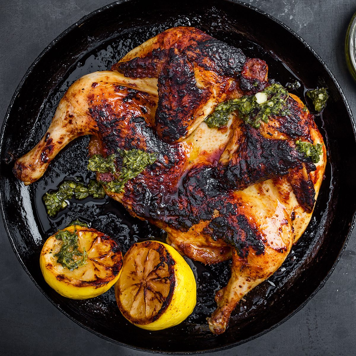 Barbequed chicken with chimichurri sauce in rustic cast iron pan on gray ready to eat, top view