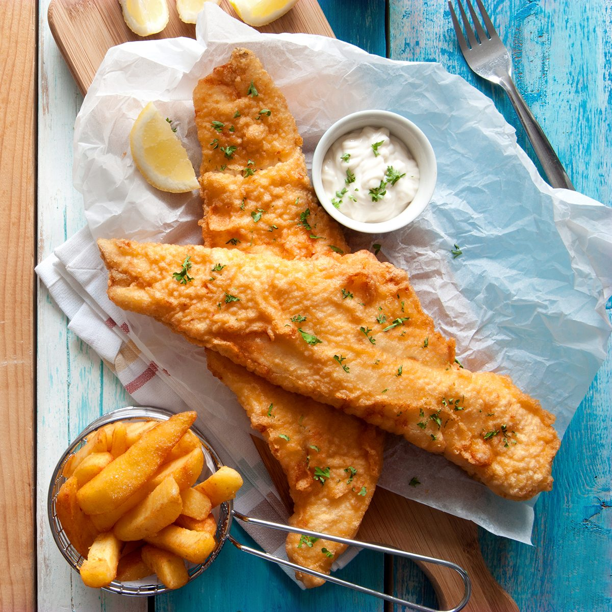 Traditional British fried fish in batter with chips in a basket