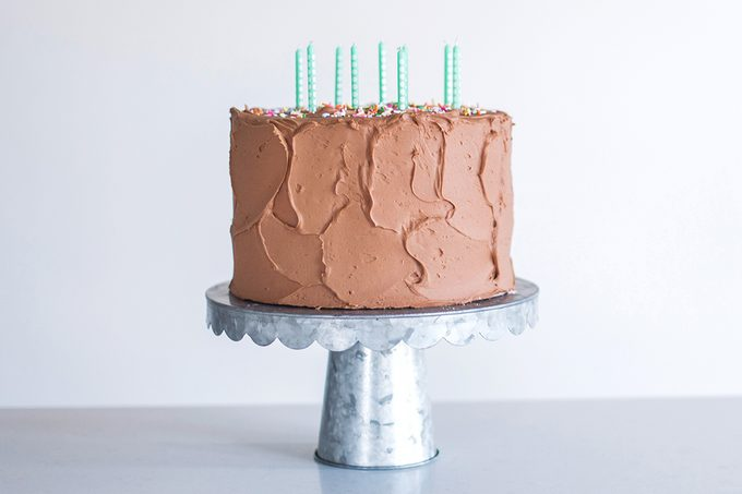Birthday cake on cake stand with gray background.