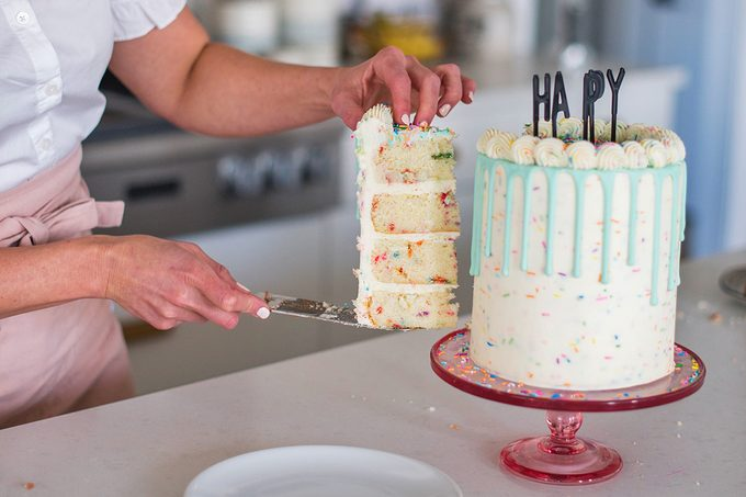 Tall layered birthday cake with drip icing being cut.