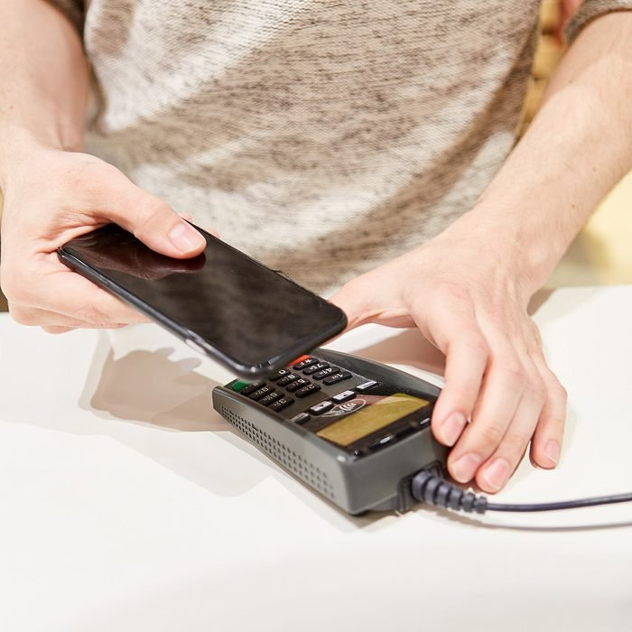 Customer at the checkout makes mobile payment with the smartphone