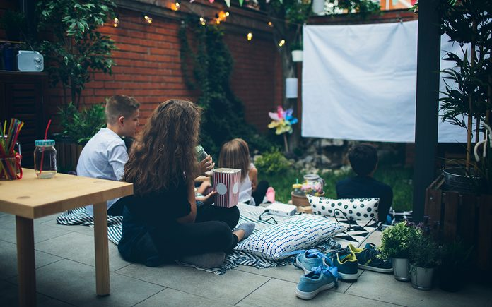 Group of children on movie night in backyard. Sitting on pillows, eating popcorn and watching movie.