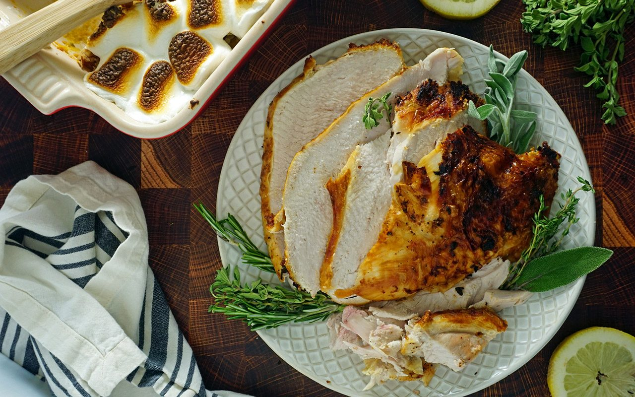 carved air fryer turkey breast on a platter with herbs and sweet potato casserole overhead