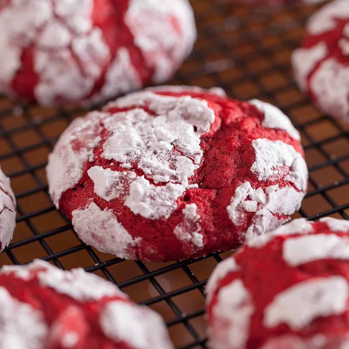 Red velvet crinkle cookies cooling on a baking rack for Christmas holiday baking