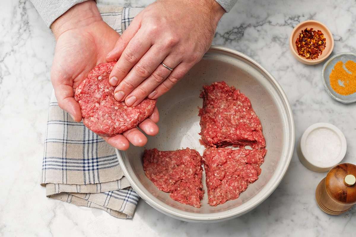 Easy Grilled Hamburgers; How to; marble surface; overhead camera angle; marble surface; burgers; burger; hamburger; hamburgers; hands; prep; in process; mixing bowl; ground beef; patty; patties; wax paper; step #2 disk of meat divided with four sections marked; one section removed and being formed into patty with hands; raw beef; uncooked; spices; spice; salt; red pepper flakes; striped cloth; cloth