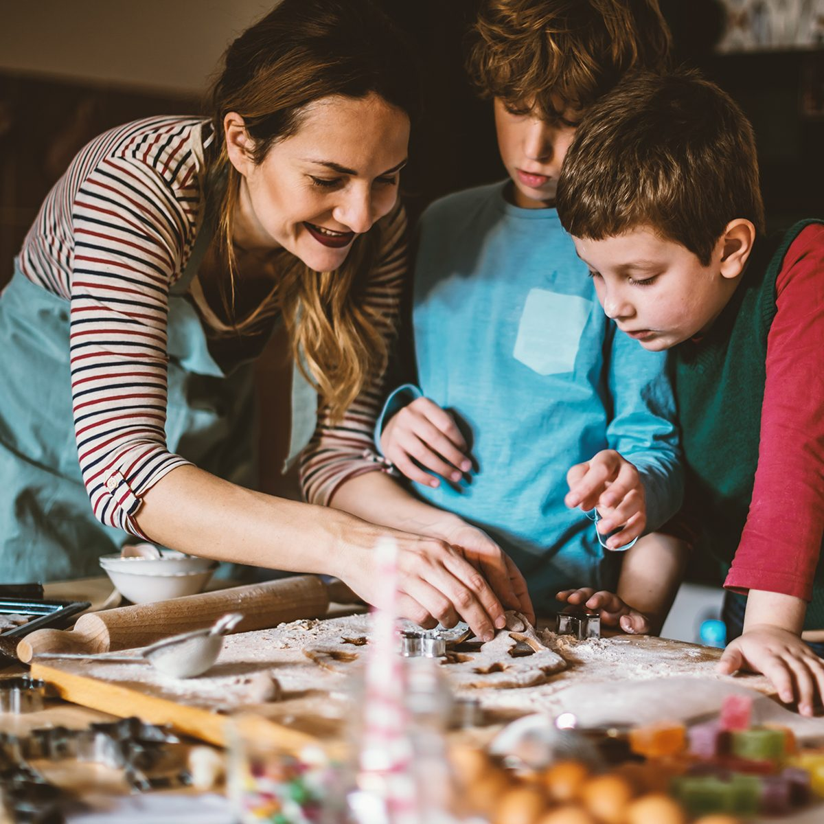 Mother and Children making Gingerbread cookies for Christmas.They enjoy in Christmas moments.