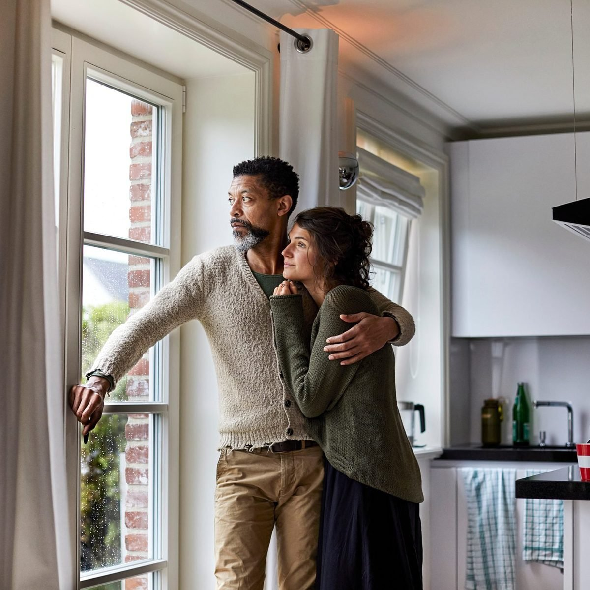 Pensive man embracing young woman looking out of window in kitchen