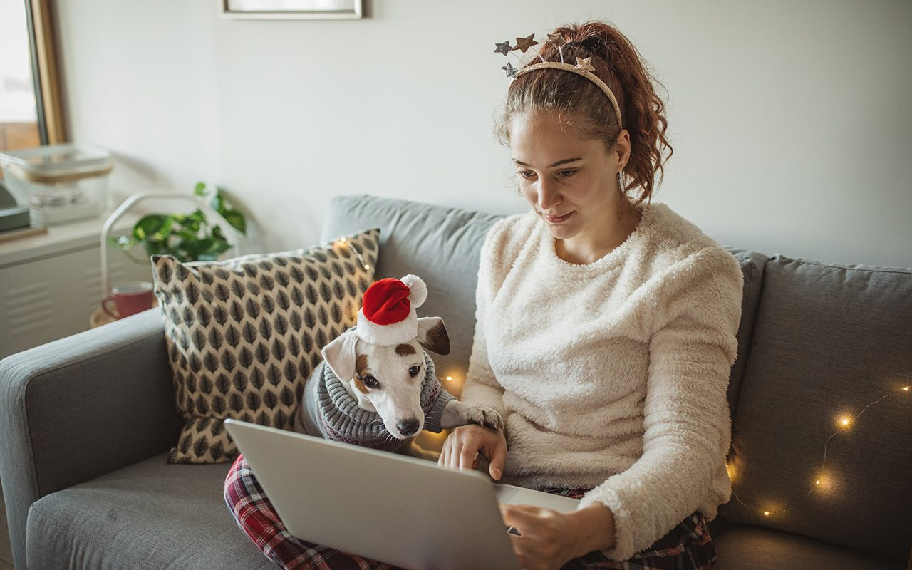 Young woman celebrating New Year at home with her dog. Dog is wearing costume, she is smiling and enjoy in holiday. Woman using laptop for online shopping