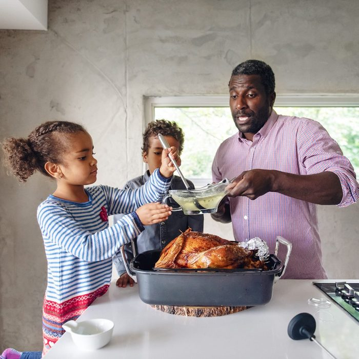 Fathers preparing thanksgiving turkey with his kids