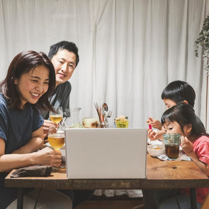 Asian family attending online video call and enjoying dinner together.