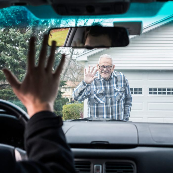 Grandson and Grandpa waving goodbye. A smiling senior adult elderly man grandfather wearing a plaid lumberjack shirt is waving to his college student grandson through the car windshield. The young man is waving back. He is about to leave the family home for some errands before driving back to his college campus apartment.