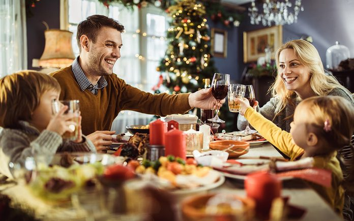 Happy family enjoying in celebratory toast during Christmas dinner at dining table. Focus is on parents.
