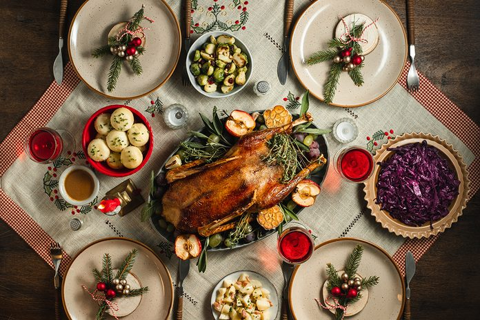 Top view of traditional german christmas dinner served on table. Christmas eve menu of roasted duck, dumplings and red cabbage with red wine on decorated dining table.