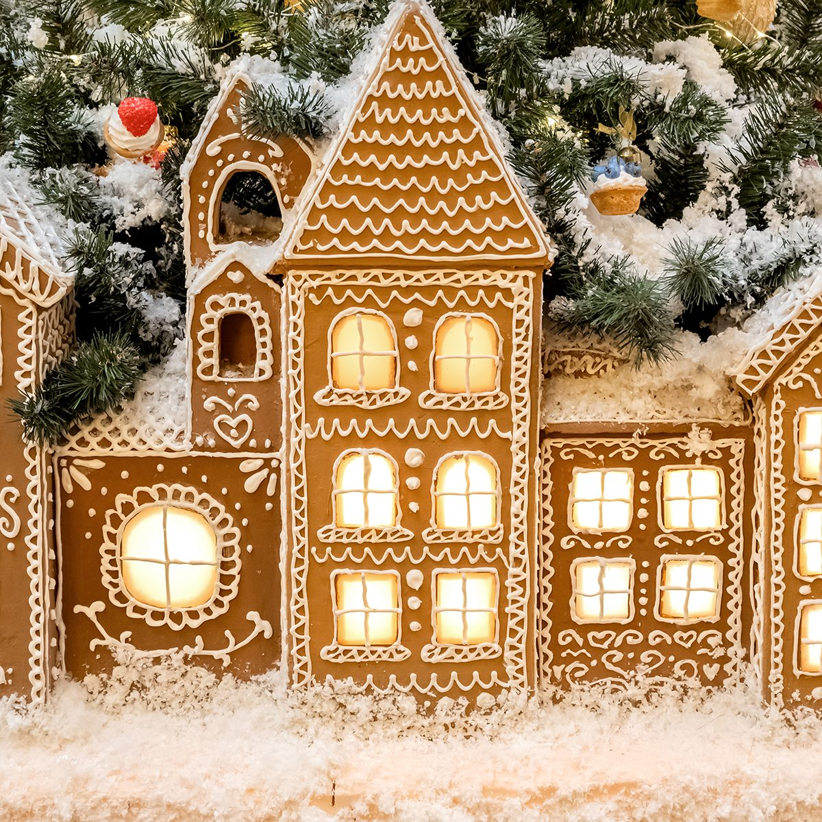 Christmas gingerbread houses with light from the windows standing in a row holiday background.