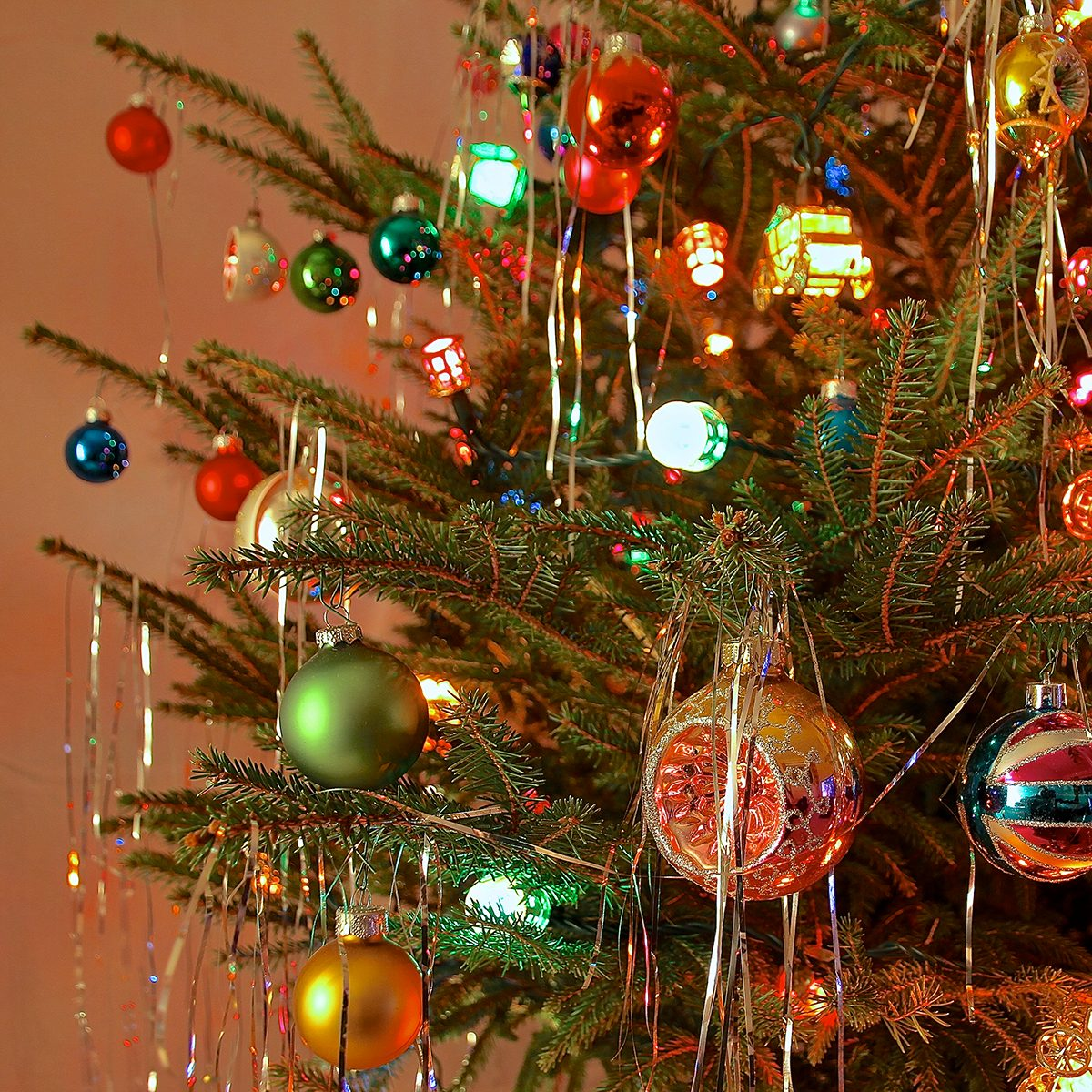 Close up of Christmas Tree decorated with antique glass baubles and coloured lights in kitsch retro 70s style