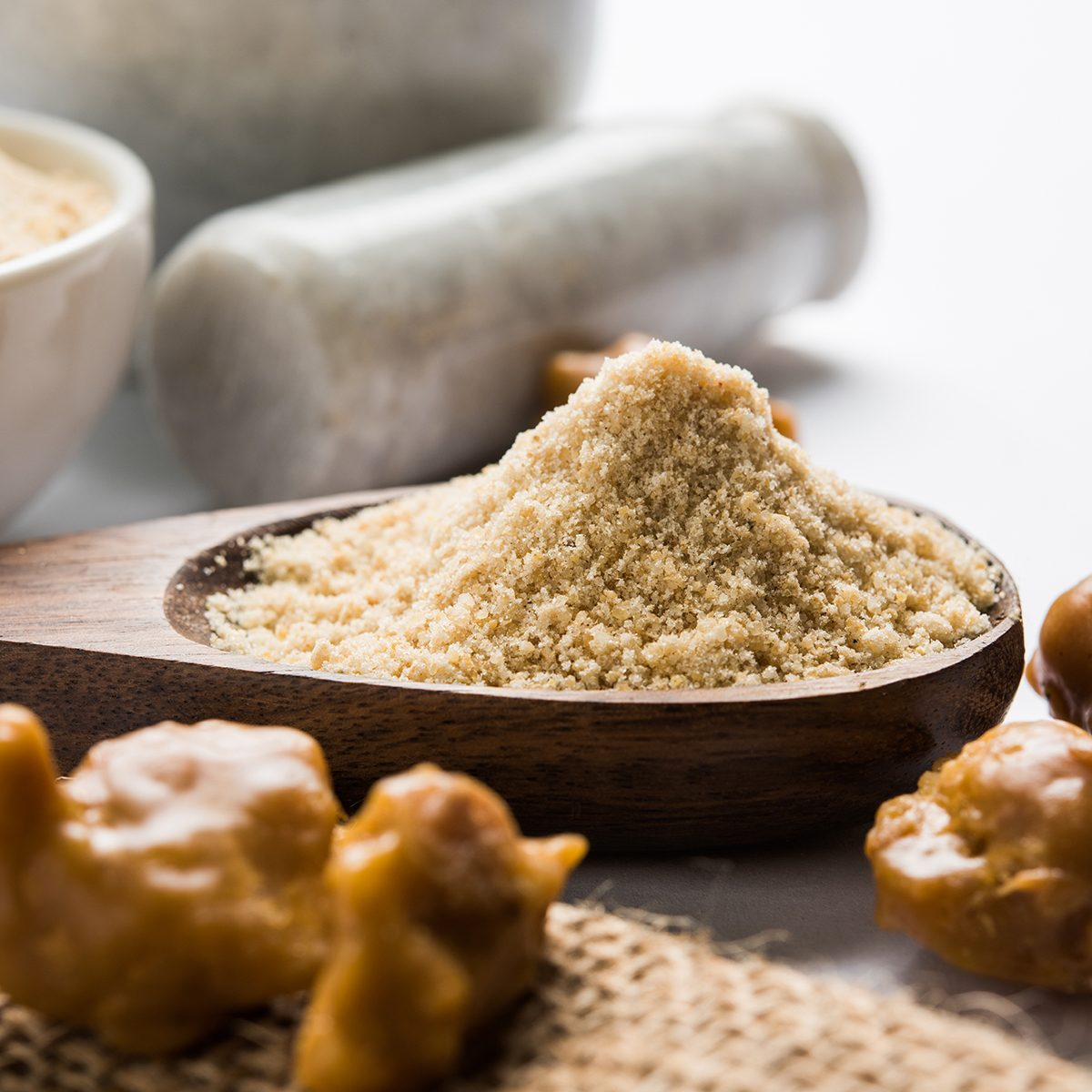 indian spices Asafoetida cake and powder or Hing or Heeng which is an important ingredient in Indian food recipes with big wooden spoon and mortar, selective focus