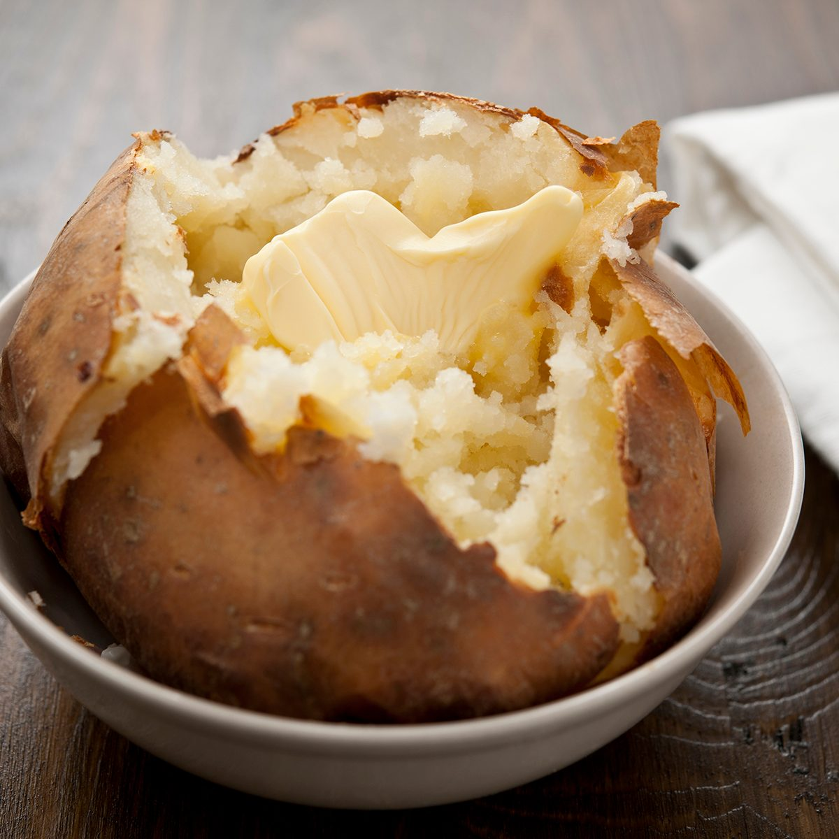 Baked potato with melting butter, horizontal.