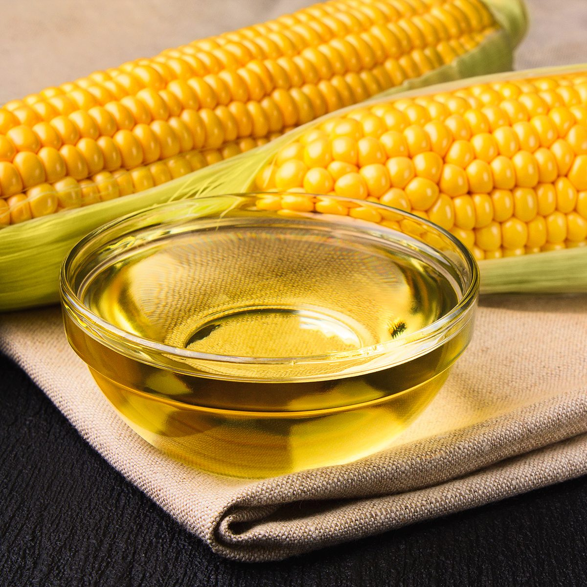 Fresh corn oil in a bowl with ears of corn on a cloth on a slate background