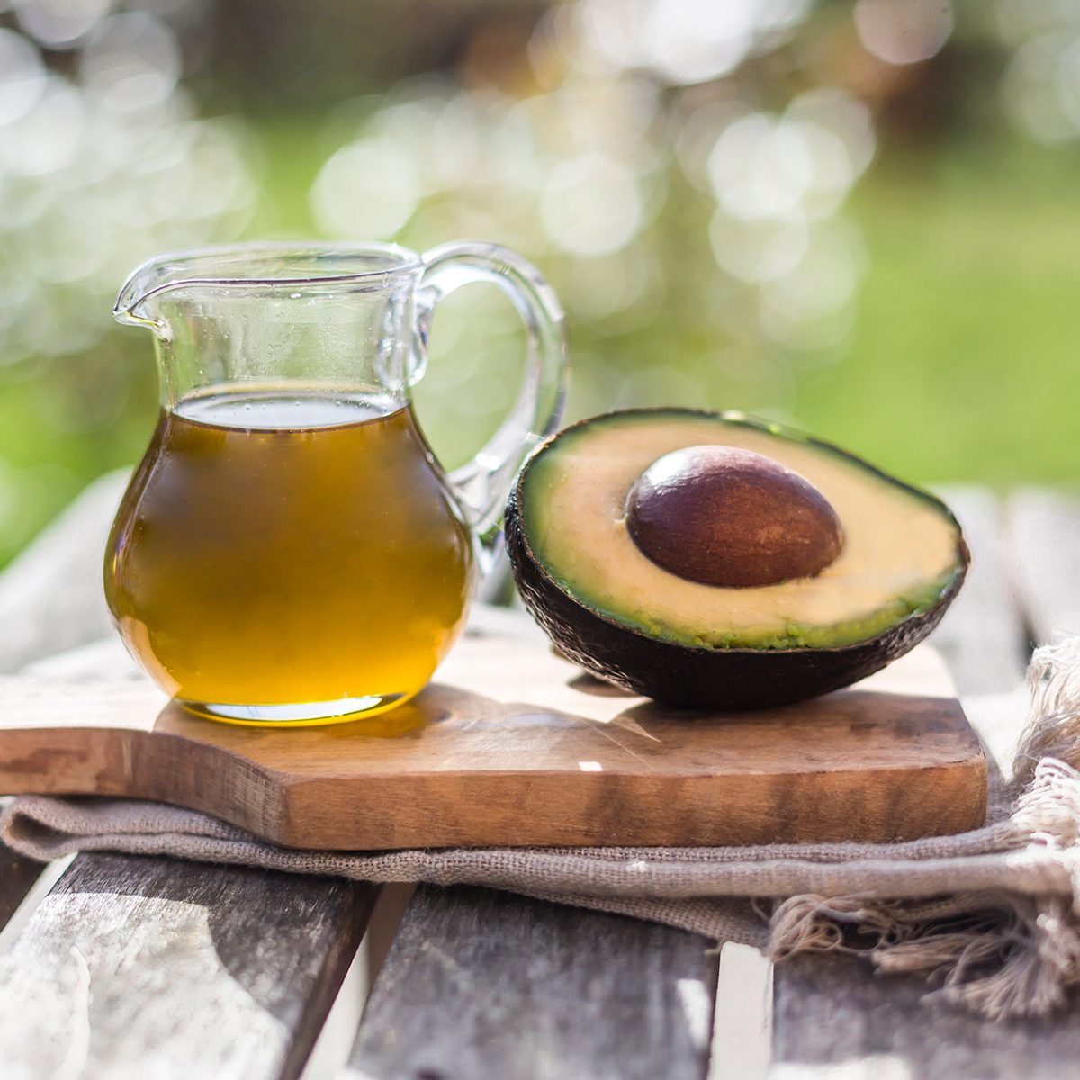 healthy oils Half of avocado and glass jug of avocado oil on wooden board