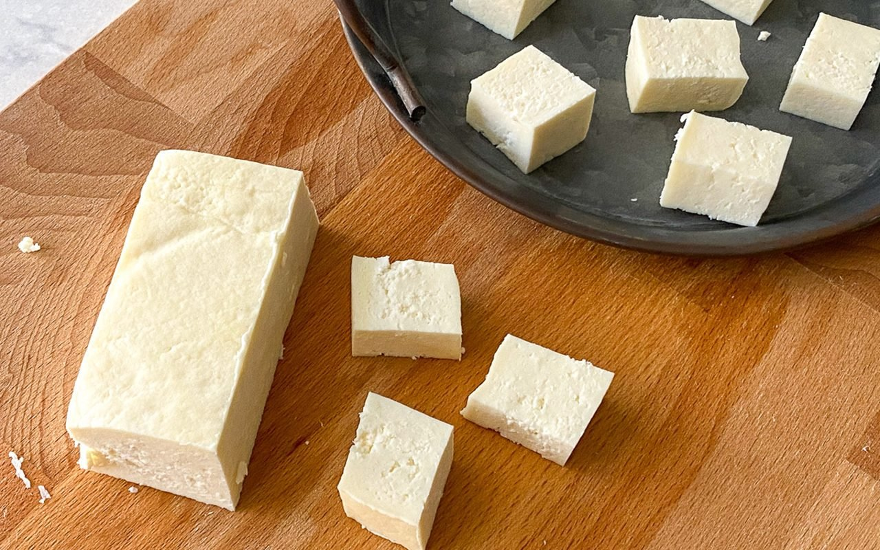 Fresh paneer cut into cubes and blocks placed on a cutting board and serving tray