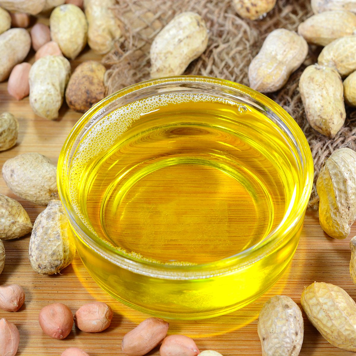 Peanut oil also known as groundnut oil in a glass cup and peanuts on the background.