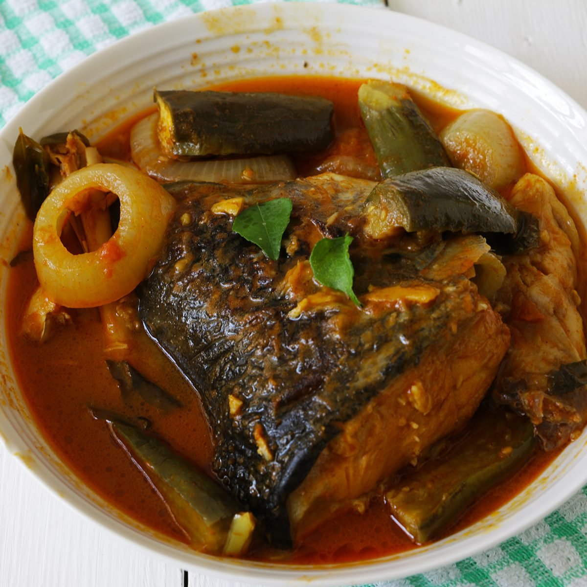 indian main dishes Spicy Salmon fish head curry with onion and eggplant on white wooden table