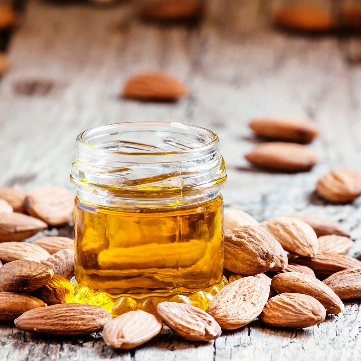 healthy oils Sweet Almond Oil, first extraction, in a small glass jar, dry almond nuts on an old wooden background, selective focus