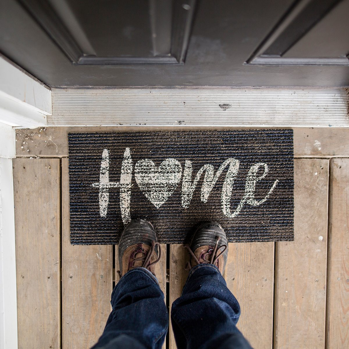 Close Up Of Person Standing On Doormat At The Entry Of A Home