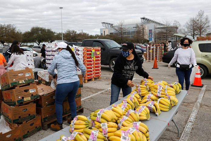 HOUSTON, TEXAS - FEBRUARY 21: Volunteers prepare to load food into cars during the Houston Food Bank food distribution at NRG Stadium on February 21, 2021 in Houston, Texas. Thousands of people lined up to receive food and water at a mass distribution site for Houston residents who are still without running water and electricity following winter storm Uri. The storm swept across 26 states with a mix of freezing temperatures and precipitation, knocking out power to millions across the state. (Photo by Justin Sullivan/Getty Images)