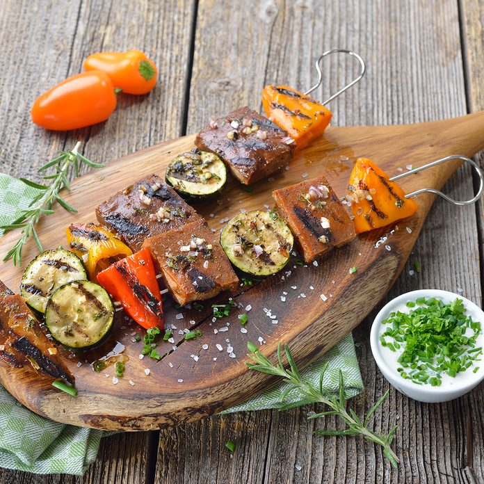 best meat substitutes Vegan meal: Grilled skewers with mixed vegetables and seitan served on a wooden cutting board with a herb soy sauce